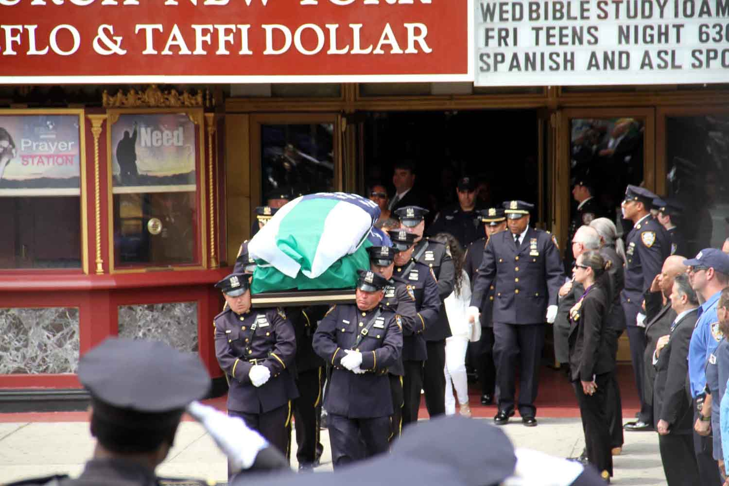 The body of of police officer Miosotis Familia is taken from the church to Woodlawn Cemetery.--Photo by David Greene