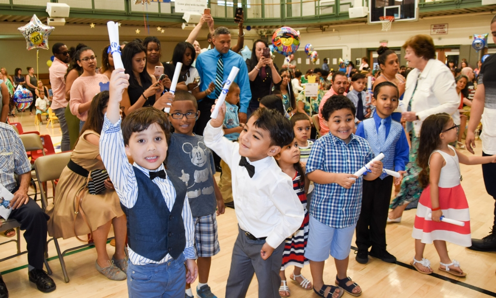 Delighted Bronx preschoolers from the New York Institute for Special Education (NYISE) celebrate with their diplomas as their proud parents take photos following the school's 2017 Readiness program graduation ceremony on June 20. (Photo Credit: James Rivera)