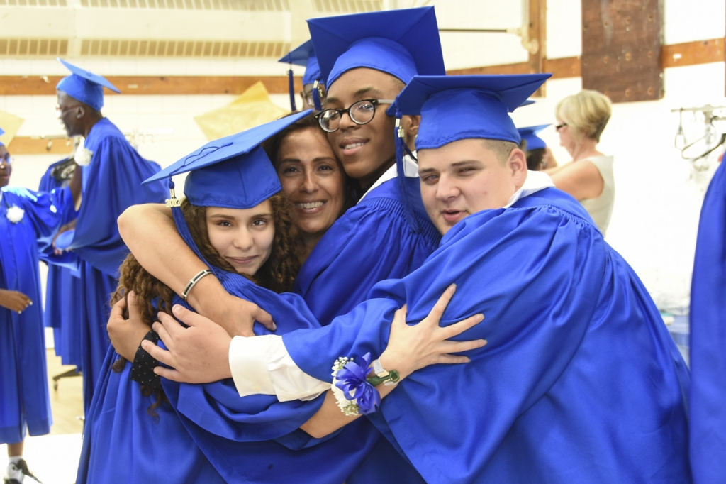 Proud New York Institute for Special Education (NYISE) graduates celebrate with a group hug following the 2017 graduation ceremony for the school's Schermerhorn and Van Cleve programs on June 21. (Photo Credit: James Rivera)