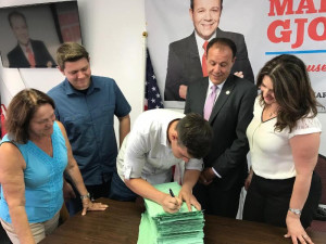 Assemblyman Mark Gjonaj and his family stand by as his son, Nicholas, adds his signature to the stack of designating petitions. (L-R) Roza Gjonaj, Joseph Gjonaj (16), Nicholas Gjonaj (18), Assemblyman Gjonaj, Roberta Gonaj.