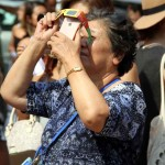 A woman takes photos of the eclipse with her cellphone outside of the Pelham Bay library.--Photo by David Greene