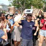 A crowd gathers around a man who designed his own special eclipse viewing glasses in Pelham Bay.--Photo by David Greene