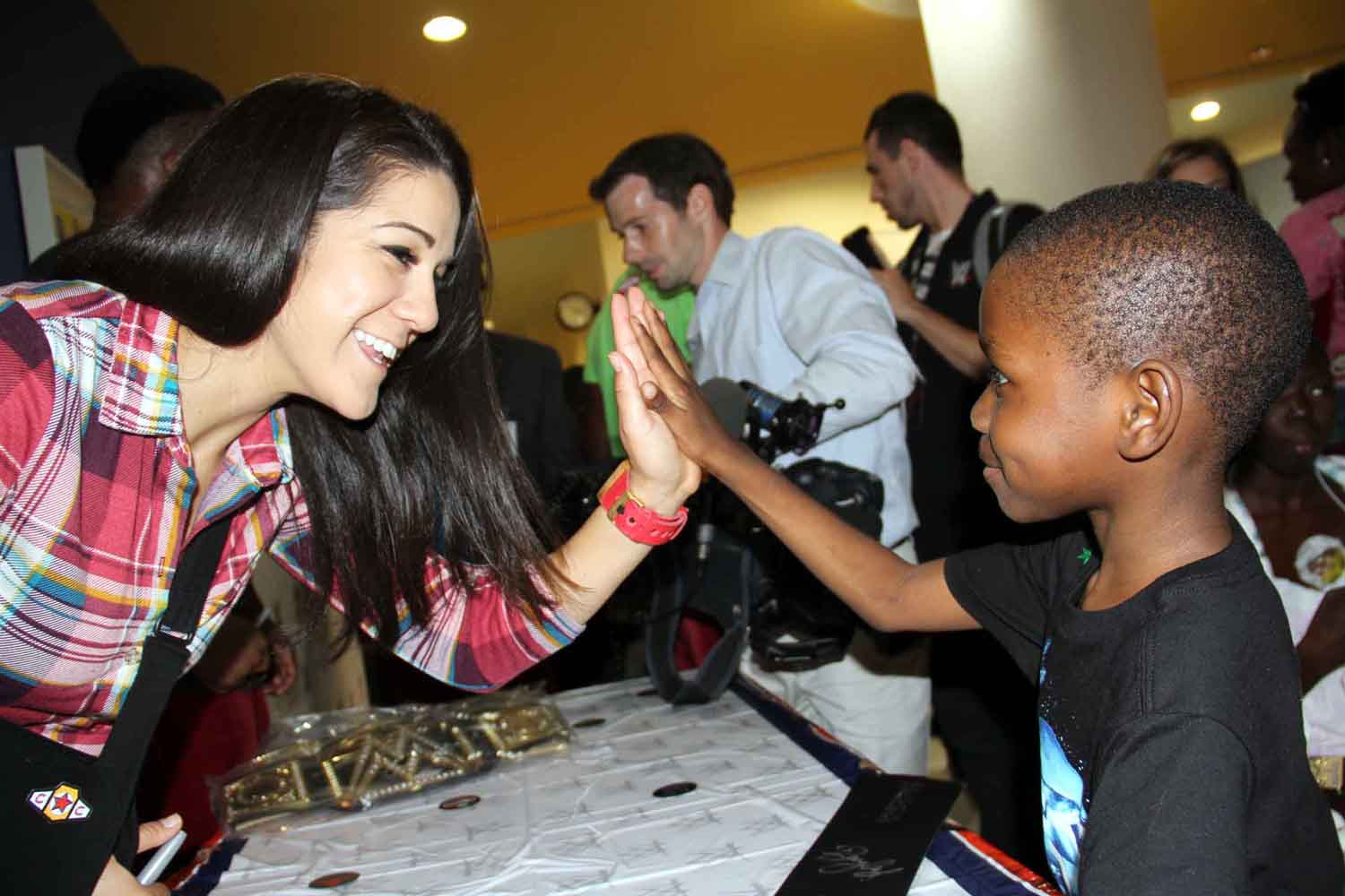 Advul Barrie, 7, gets a high-five from WWE star Bayley.--Photo by David Greene