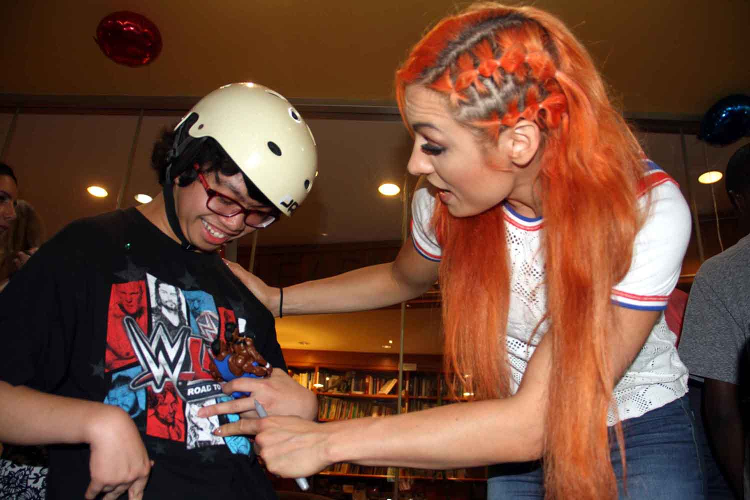 WWE star Becky Lynch admires WWE shirt of Clarence Aguire, 15.--Photo by David Greene