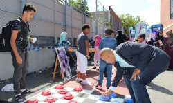 Bronx Borough President Ruben Diaz Jr. plays a game of checkers with 16-year-old Rafa Shahbaim of Harding Park during the borough president's annual Muslim School Holiday Event, which took place at P.S. 83 in Morris Park on Saturday, September 9, 2017