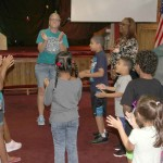 Youngsters of all ages join in for a song at the end of the summer program.--Photo by David Greene