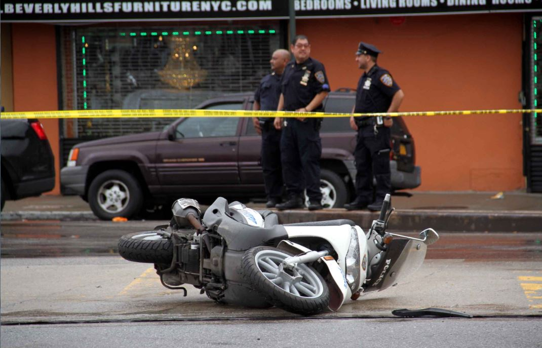 Two of the four cars involved and the police scooter lies on the ground along East Tremont Avenue on Sunday. Photo by David Greene