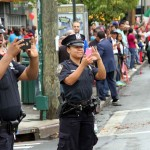 A pair of NYPD police officers capture a moment of the Bronx Columbus Day Parade on their cellphones.--Photo by David Greene
