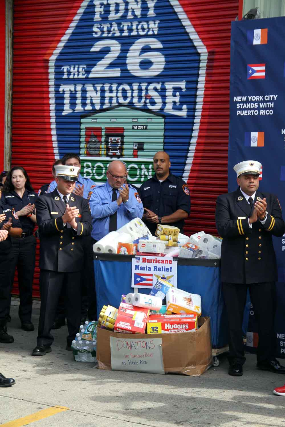 FDNY brass stand with donated items headed for Puerto Rico.--Photo by David Greene
