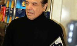 Actor Chazz Palminteri holds a framed street sign from his new collection.--Photo by David Greene
