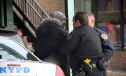 Police restrain and question accused shoplifter Ronald Kinard outside of Duane Read on East Kingsbridge Road.--Photo by David Greene