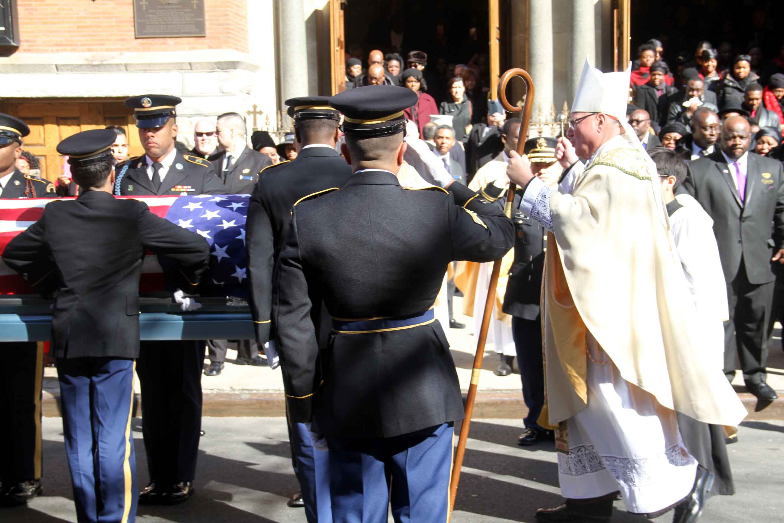 Cardinal Timothy Dolan sprinkles holy water on the flag-draped coffin of Private First Class Emmanuel Mensah. Photo by David Greene