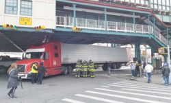 A tractor-trailer gets wedged under the elevated subway after striking and damaging a pillar along Westchester Avenue.--Photo by Edwin Soto