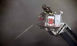 Members of Tower Ladder 33 battle the blaze from above despite the thick, black smoke.--Photo by David Greene