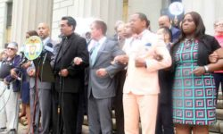 Elected officials join arms with community and clergy leaders in denouncing the current White House policy on immigration.--Photo by David Greene
