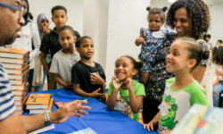Kids and families get copies of The Crossover and Surf's Up signed by author Kwame Alexander. At Success Academy's Robertson Center in Hudson Yards, Manhattan, on June 28, 2018.