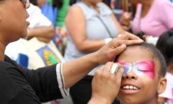 A happy girl enjoys the free face-painting during the 52nd Precinct's National Night Out at Poe Park.--Photo by David Greene