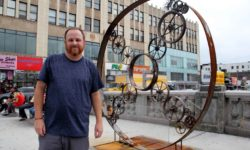 "Artist and welder Colin Nicodemo, 44, proudly stands next to his creation titled, ""All Roads Lead to Fordham"" on the Grand Concourse.--Photo by David Greene"