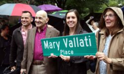 "Family members hold the new street sign unveiled naming the intersection of East Mosholu Parkway South and Perry Avenue ""Mary Vallati Place.""--Photo by David Greene"