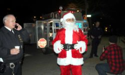 NYPD's Auxiliary Inspector David Wong of the 52nd Precinct (left) joins Santa Clause and members of the Emergency Services Unit on the Grand Concourse.--Photo by David Greene