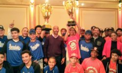 BP Diaz Jr., coaches, players hold up the two trophy's.