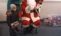 Santa is helped by one of his Elfs to distribute his presents to the children.
