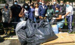 The volunteers stand behind the full trash bags and other trash that was picked up by the Parks Department.