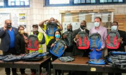 All who participated in the Book Bag Food Giveaway hold a book bag that was given away.