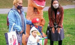 Congresswoman Ocasio-Cortez with Ms. Abilene Salas and Lorenzo, Dante, and Valerie in the dinosaur costume.