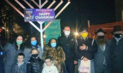 A group photo with Rabbi Pewzner's children in the front row, (L - R) Rabbi Pewzner's wife, Assemblywoman Fernandez, District Leader Estrada, Councilman Gjonaj, Steve Glosser of the BJCC, Rabbi Pewzner, and Assemblyman Benedetto in front of the menorah with just the middle and right candles lit on the first day of Chanukah.