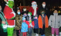 A group photo with Santa, the Grinch, Councilman Mark Gjonaj, District Leader Irene Estrada, Camelia Tepelus of the Morris Park BID, and some of the children on hand.