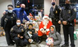 Santa with His 'Elves in Blue', and some children who received toys from Santa.